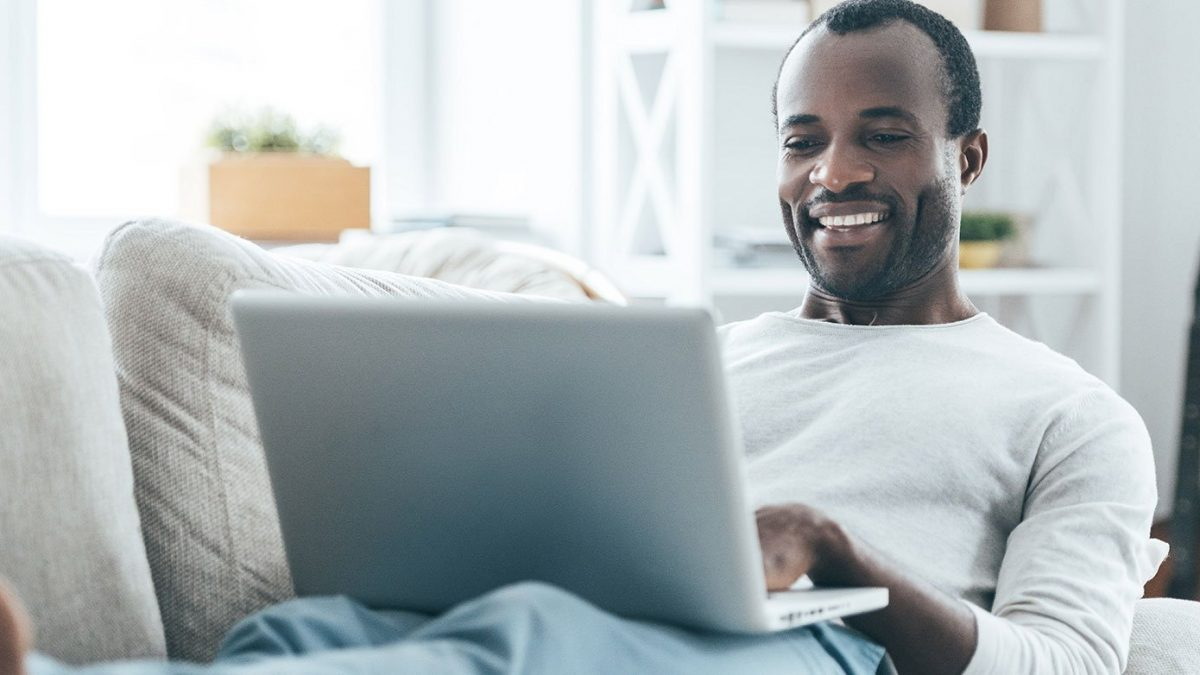 Man on computer laying on the couch